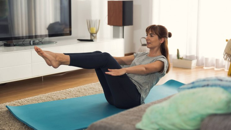 Eine Frau macht zu Hause Übungen für ihre Fitness.