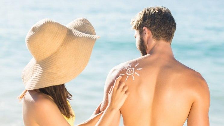 Eine junge Frau cremt den Rücken eines Mannes ein, um ihn vor Sonnenbrand zu schützen.