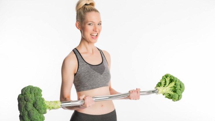 Eine Vegetarierin macht mit einer Brokkoli-Hantel Sport