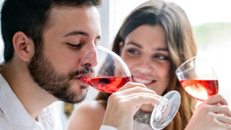Paar mit Glas Rotwein: Wenig Alkohol hilft der Gesundheit