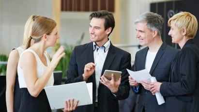 Mehrere stehende Business-Geschäftsleute unterhalten sich angeregt