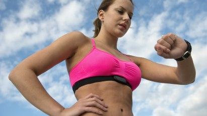 Eine Frau misst ihrem Puls beim Joggen.