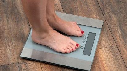 BMI: eine Frau steht auf einer Waage.
