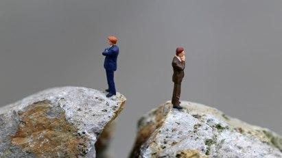 Zwei Figuren stehen mit dem Rücken zueinander auf zwei Hügeln aus Plastik