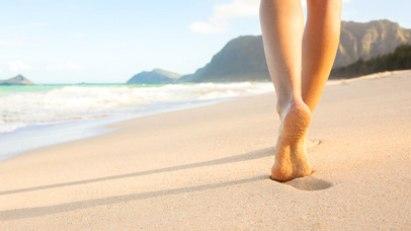 Frau läuft barfuß am Strand: Barfußlaufen tut den Füßen gut