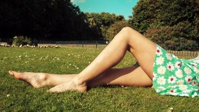 Frau liegt in Wiese: Thromboseschutz - lieber liegen und laufen als stehen und sitzen