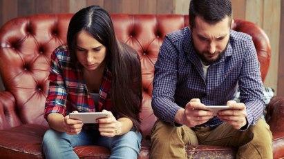 Mann und Frau mit Smartphones - nicht nur auf das Handy starren beugt Handynacken vor