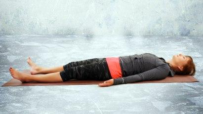 Frau liegt auf Rücken: Yoga in Rückenlage entspannt Körper und Geist