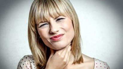 Frau mit Erkältung verzieht das Gesicht wegen starker Halsschmerzen.