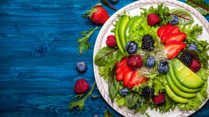 Teller mit Salat, Erdbeeren und Blaubeeren: Obst und Gemüse helfen beim Abnehmen