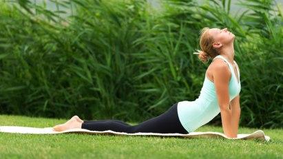 Frau beim Yoga im Grünen: Yoga hilft bei psychischen Störungen
