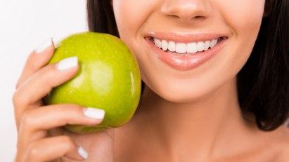 Frau mit Apfel: Gesunde Zähne dank gesunder Ernährung