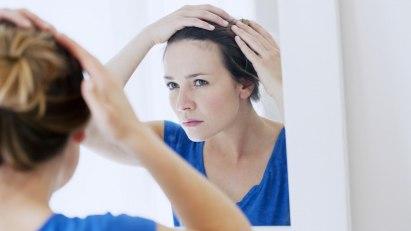 Frau begutachtet im Spiegel ihre Geheimratsecken.