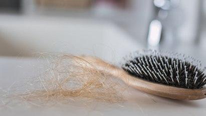 Haarbüschel vor Bürste – wie können Sie Haarausfall vorbeugen?