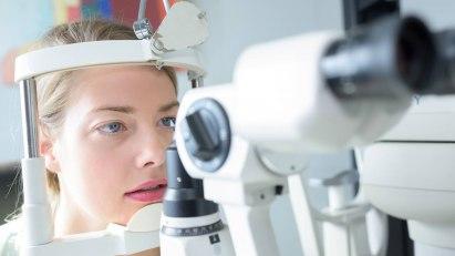Eine Frau wird von einem Arzt auf Augenflimmern untersucht.