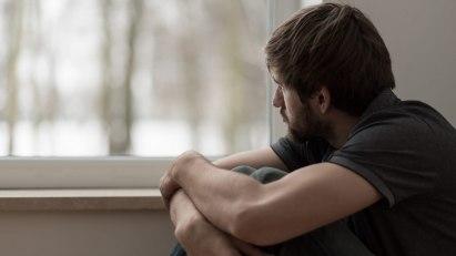 Mann sitzt verzweifelt am Fenster: Sein Erektionsproblem ist psychisch bedingt.