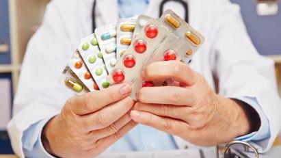 Arzt hält eine Auswahl potenzsteigernder Mittel in den Händen.