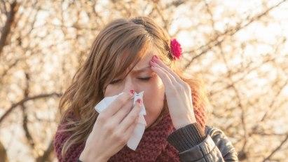 Eine Frau mit Erkältung schnäuzt sich.