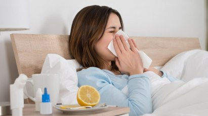 Eine Frau mit Erkältung behandelt ihre Symptome mit Medikamenten und Hausmitteln.