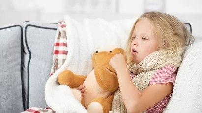 Kleines Mädchen mit Erkältung hat Husten und liegt auf dem Sofa.