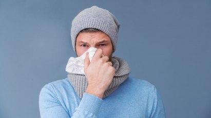 Erkältung mit gelbem Schleim: Mann mit Schnupfen putzt sich die Nase.