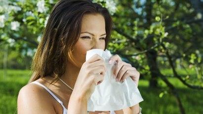 Frau benutzt ein Taschentuch, da sie eine Erkältung im Sommer hat.