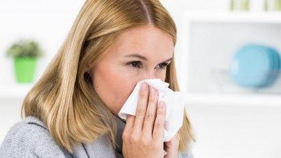 Symptome einer Erkältung: Eine Frau schnäuzt sich in ein Taschentuch.