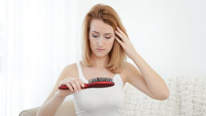 Eine junge Frau mit Haarausfall blickt auf ihre Haarbürste.