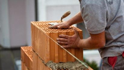 Maurer errichtet Wand ohne Schutzhandschuhe: Eine Maurerkrätze kann als Berufskrankheit anerkannt werden.