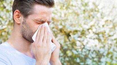 Mann putzt sich im Freien die Nase: Allergischer Schnupfen ist eine der Schnupfenarten.