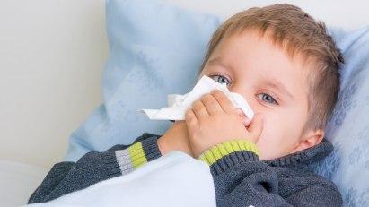 Kind putzt sich die Nase und versucht, seinen Schnupfen loszuwerden.