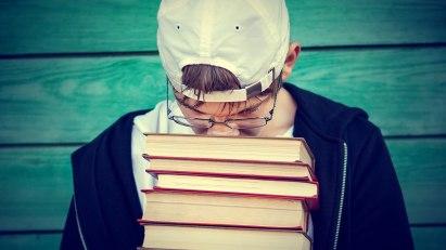 Ein Junge lässt verzweifelt seinen Kopf auf einen Stapel Bücher sinken – er leidet unter Prüfungsstress.