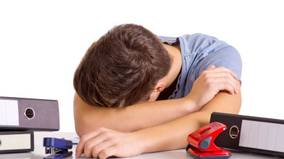 Ein junger Mann beugt sich verzweifelt über seine Lernunterlagen. Er hat Prüfungsangst.