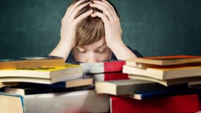 Eine Junge sitzt verzweifelt vor einem Berg Bücher – Prüfungs- und Versagensangst plagen ihn.