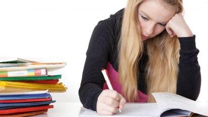Eine Frau sitzt mit unglücklichem Gesicht über ihrem Lernmaterial: Verzweiflung ist ein typisches Prüfungsstress-Symptom.