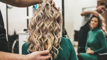 Eine Frau ist beim Friseur und lässt sich die Haare pflegen.