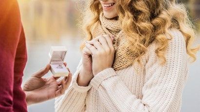 Eine Frau freut sich über den Heiratsantrag und den Verlobungsring.