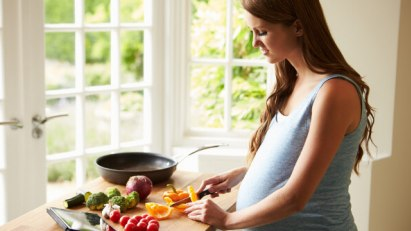 Schwangere Frau kocht vegan