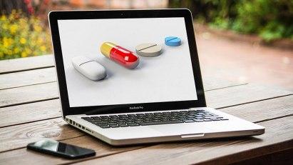 Laptop, auf dessen Display Tabletten zu sehen sind, die bildlich für Versandapotheken stehen.