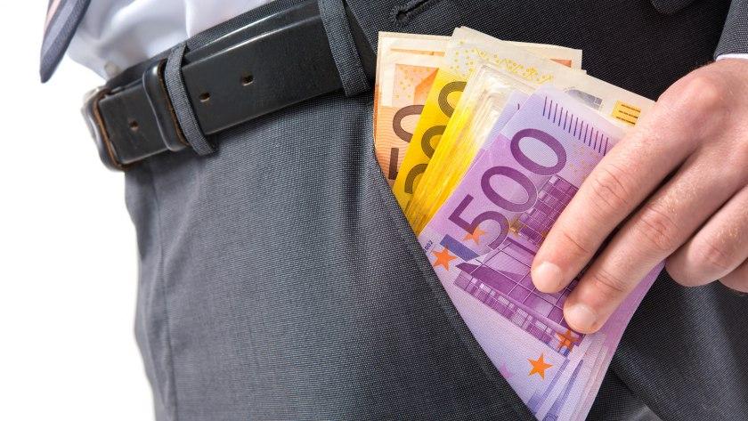 Ein Mann schiebt sich viele Euroscheine in seine linke Hosentasche.