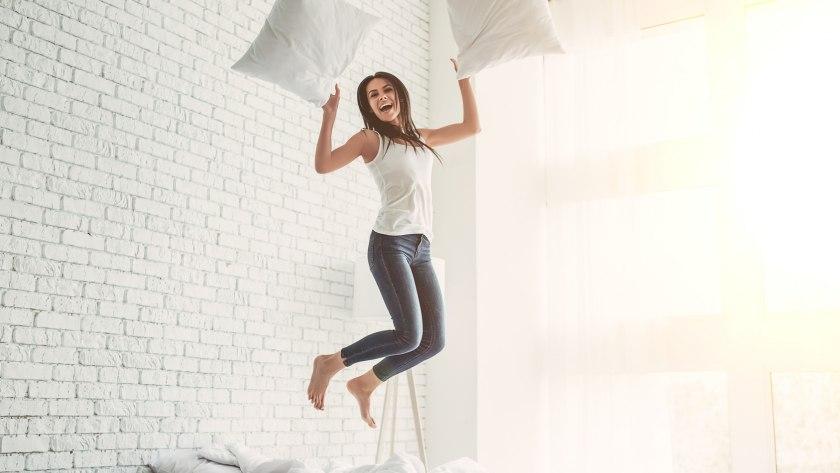 Eine junge Frau springt auf ihrem Bett: Eine gute Matratze hält auch wilde Kissenschlachten aus.